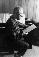 Leo Ornstein seated at his piano while looking at a score