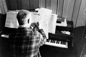 Leo Ornstein seated at his piano and marking up a score