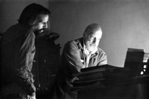 Composer James Cleghorn (right) seated at a piano as his son Peter Sloan Cleghorn looks on