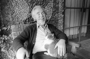 Conlon Nancarrow seated with his cat in front of Juan O'Gorman mural at his Mexico City home