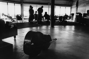 A double bass with OM 12 participants in the background