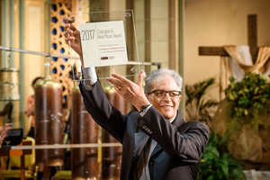 "Charles Amirkhanian holds up his ""Champion of New Music Award"" which was bestowed to him by the American Composers Forum during OM 22's second concert."